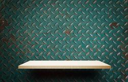 Empty wooden shelf display on metal wall. Sheet Royalty Free Stock Images