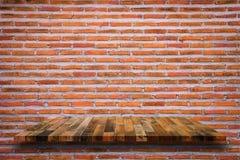 Empty wooden shelf on red brick background. Royalty Free Stock Photo