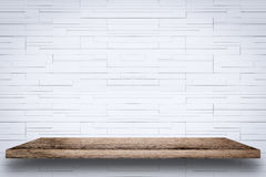 Empty wooden shelf with white brick wall background. Royalty Free Stock Photos