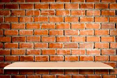 Empty wooden shelves and brick wall background for product
