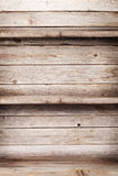 Empty wooden shelves. In front of wooden wall with copy space Royalty Free Stock Photos