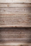 Empty wooden shelves. In front of wooden wall with copy space Stock Photos