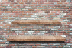 Empty wooden shelves over grunge brick wall background Stock Image
