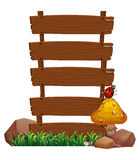 An empty wooden signboard with a bug at the top of the mushroom Royalty Free Stock Image