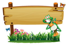 An empty wooden signboard with a playful frog Stock Image