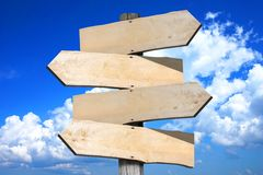Empty wooden signpost - four arrows Royalty Free Stock Image