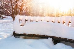 Empty wooden snow covered bench in the town square stock photos
