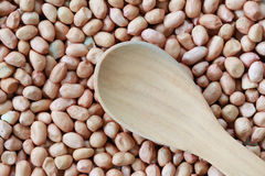 Empty wooden spoon on pile peanut background. Stock Photos
