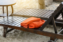 Empty wooden sunbed with orange towels on the beach. Vacation concept Royalty Free Stock Photos