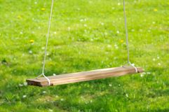 Empty Wooden Swing in the Garden Royalty Free Stock Photo