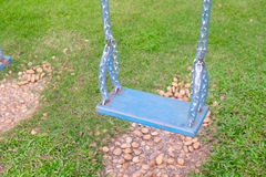 Empty wooden swing in a green park Stock Photos