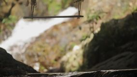 Empty wooden swing hanging by rope near waterfalls. Empty wooden swing hanging by rope stock video footage