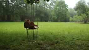 Empty wooden swing swaying slowly in the rain