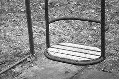 Empty wooden swings for baby or older kid at the fenced local playground. Royalty Free Stock Image