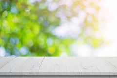 Empty wooden table and abstract blurred green bokeh leaves background texture, display montage with copy space.  stock image