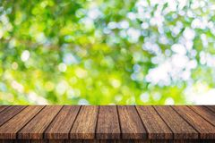 Empty wooden table and abstract blurred green bokeh leaves background texture, display montage with copy space.  royalty free stock photo