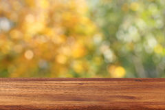 Empty wooden table against the background of autumn trees. The background is blurred Royalty Free Stock Photos
