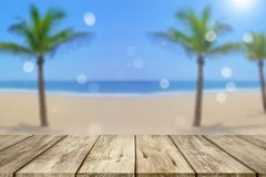 Wooden table with blurred beach background stock photography