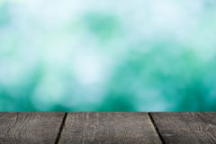 Empty wooden table with blue bokeh background Royalty Free Stock Photos