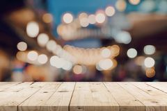 Empty wooden table and blurred background at night market festival people walking on road with copy space, display montage for. Product royalty free stock images