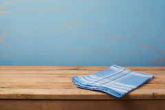 Empty wooden table with checked blue tablecloth over rustic painted wall. With copy space Royalty Free Stock Photography
