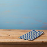 Empty wooden table with checked blue tablecloth over rustic painted wall Royalty Free Stock Photo