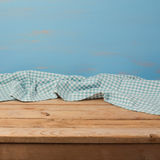 Empty wooden table with checked blue tablecloth over rustic painted wall Stock Photo