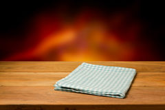 Empty wooden table with checked tablecloth over blur fire background. Royalty Free Stock Photos