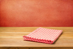 Empty wooden table with checked tablecloth over grunge red concrete wall. Stock Images