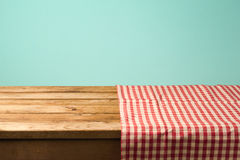Empty wooden table covered with red checked tablecloth. Background for product montage. Display Stock Photo