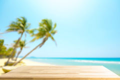 Empty Wooden table for display product and blurry beautiful beach in background. Abstract background stock photography
