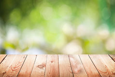 Empty wooden table with foliage bokeh Royalty Free Stock Photo