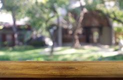Empty wooden table in front of abstract blurred green of garden and house background. For montage product display or design key royalty free stock photos