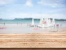 Empty wooden table in front with blurred background at the beach. And sailboat,space for montage you products royalty free stock images