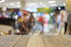 Empty wooden table on front blurred shopping mall background. Used for template and presentation product stock photography
