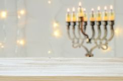 Empty wooden table in front of jewish holiday Hanukkah background with menorah & x28;traditional candelabra& x29;. For product display stock photo