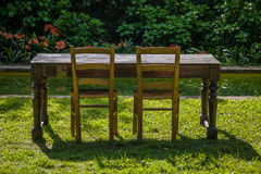 Empty wooden table with garden and two chairs for food. Outdoor Royalty Free Stock Photography