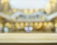Empty wooden table over blurred mall bokeh background Stock Image