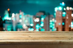 Empty wooden table over night city bokeh. Background stock image