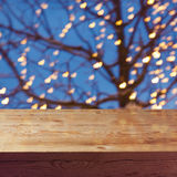 Empty wooden table over night lights decoration and tree background Royalty Free Stock Images