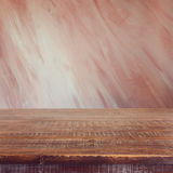 Empty wooden table over painted marsala color wall Royalty Free Stock Images