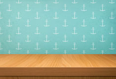 Empty wooden table over vintage wallpaper with a pattern of anch Royalty Free Stock Image