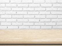 Empty wooden table over white brick wall. Empty wooden table over white brick wall background royalty free stock photo