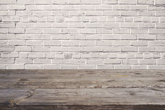 Empty wooden table over white brick wall. Background for product montage stock image