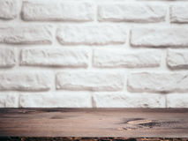Empty wooden table over white brick wall. Background for product montage display. Empty wooden table over white brick wall as background. Brown wooden background royalty free stock image