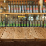 Empty wooden table over wine store background Stock Photos