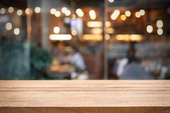 Empty wooden table and Photo of blurred restaurant or cafe. royalty free stock image