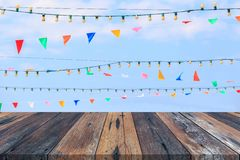 Empty wooden table or plank with blue sky and clouds and colorful paper flag on background for product display. Copy space available stock photo