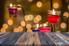 Empty wooden table or plank with bokeh of light from red candle in glass tree on background. stock photography
