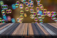 Empty wooden table or plank with bokeh of rainbow soap bubbles from the bubble blower on background for product display. Copy space available royalty free stock photo